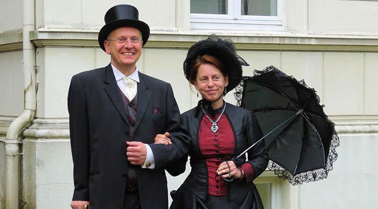 """Angelehnt an die historischen Vorbilder trägt das """"Ehepaar Steinmeister"""" bei seinen Spaziergängen durchaus """"standesgemäße"""" Kleidung."""