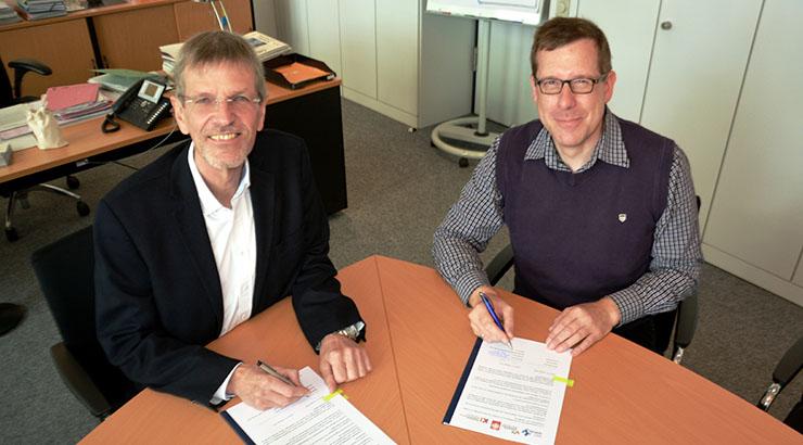 Unterschreiben gemeinsam den Kooperationsvertrag für Muttersprachliche Assistenten: (v.l.) Norbert Burmann (Dezernent Kreis Herford) und Richard Knoke (Vorstand des Herforder Caritasverbandes)