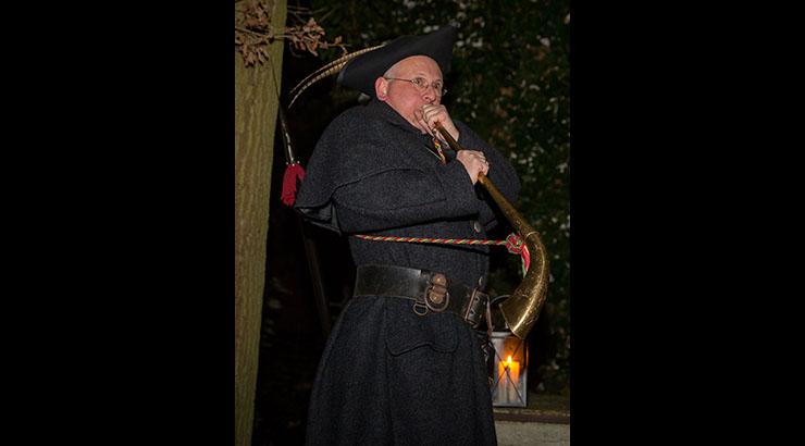 """Neben Hellbarde und Laterne zählte ein Horn – in das das Bünder Original Friedrich """"Papa"""" Frentrup hier zu stoßen versucht – stets zur Ausrüstung der historischen Nachtwächter. (Foto: A. Klüter)"""
